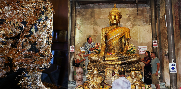 placing gold leaf on buddah in wat